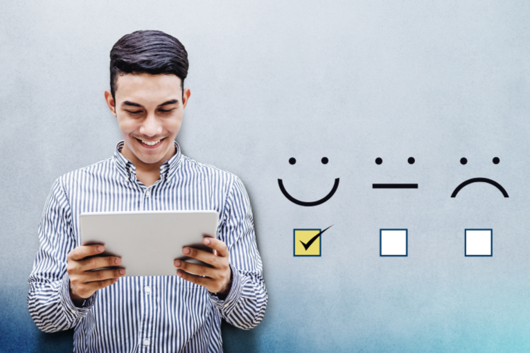 A man is smiling while looking at a piece of paper. Three happy, meh, unhappy icons are to his right; the happy one is checked.