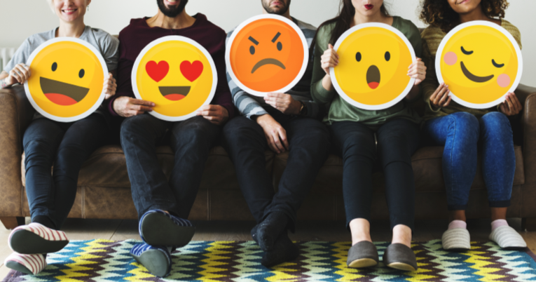 a group of people sitting and holding social media emojis